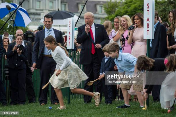 President Donald Trump with first lady Melania Trump their son Barron Trump and members of the first family blows a whistle to begin an Easter Egg...