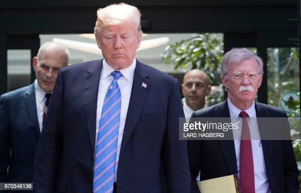 US President Donald Trump with National Security Advisor John Bolton and White House Chief of Staff John Kelly leaves the G7 summit in La Malbaie...