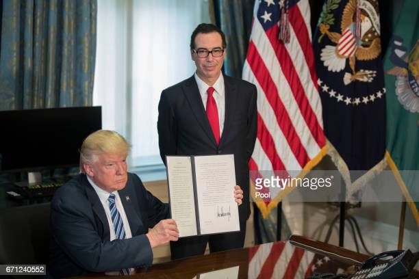 US President Donald Trump with Secretary of Treasury Steven Mnuchin displays a signed financial services Executive Order during a ceremony in the US...