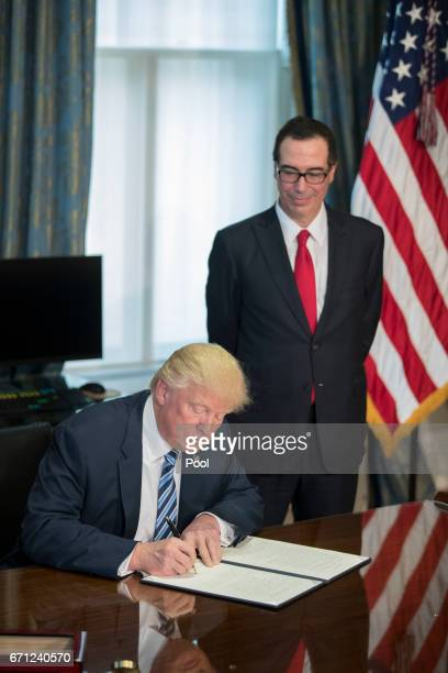 US President Donald Trump with Secretary of Treasury Steven Mnuchin signs a financial services Executive Order during a ceremony in the US Treasury...