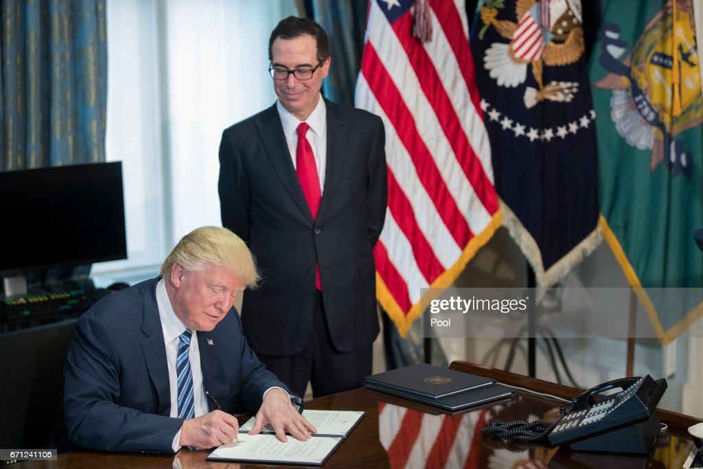 U.S. President Donald Trump (L), with Secretary of Treasury Steven Mnuchin (R), participate in a financial services Executive Order signing ceremony in the US Treasury Department building on April 21, 2017 in Washington, DC. President Trump is making his first visit to the Treasury Department for a memorandum signing ceremony with Secretary Mnuchin.