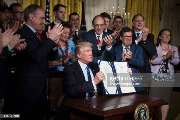 President Donald Trump with Secretary of Veterans Affairs David Shulkin by his side shows off after signing the 'Department of Veterans Affairs...