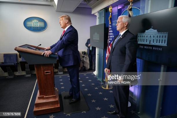 President Donald Trump with Vice President Mike Pence , delivers remarks on the stock market during an unscheduled appearance in the Brady Briefing...