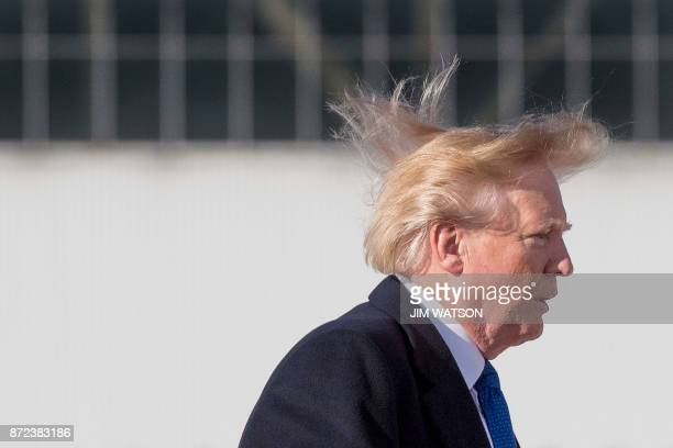 US President Donald Trump's blows in the wind as he boards Air Force One before flying to Vietnam to attend the annual Asia Pacific Economic...