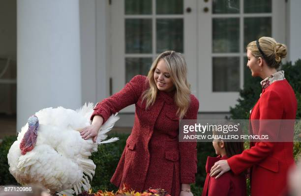 US President Donald Trump's daughter Tiffany Trump pets the turkey Drumstick as Ivanka Trump and her daughter Arabella Rose Kushner look on after the...
