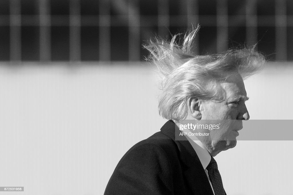 US President Donald Trump's hair blows in the wind as he boards Air Force One before flying to Vietnam to attend the annual Asia Pacific Economic Cooperation (APEC) summit at Beijing airport on November 10, 2017. /