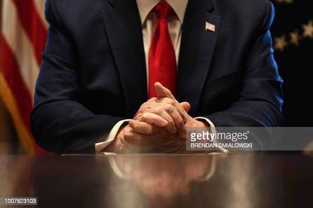 President Donald Trump's hands are seen as he speaks to the press after a meeting with nursing industry representatives on the response to the novel...