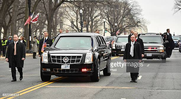 President Donald Trump's limousine moves along the route of the inaugural parade flanked by security January 20 2017 in Washington DC Donald Trump...