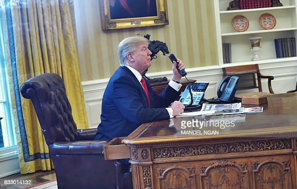 US President Donald Trumpseen through an Oval Office window speaks on the phone to King Salman of Saudi Arabia from the Oval Office of the White...