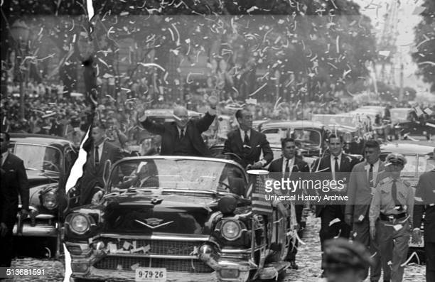 President Dwight D Eisenhower standing in automobile waving to crowds during a ticker tape parade during his visit to Rio de Janeiro Brazil