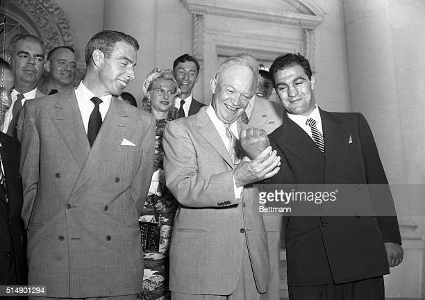 """President Eisenhower turned down the chance to feel Rocky Marciano's muscles today, telling cameramen who requested the pose """"you fellows just want..."""