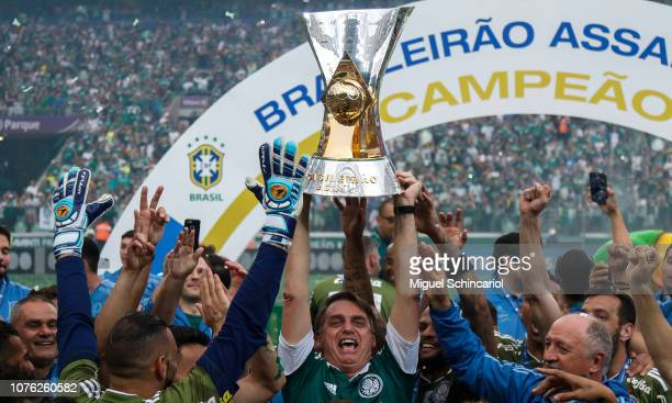 President elected of Brazil Jair Bolsonaro holds the trophy and celebrate with players of Palmeiras after winning the Brasileirao 2018 after the...