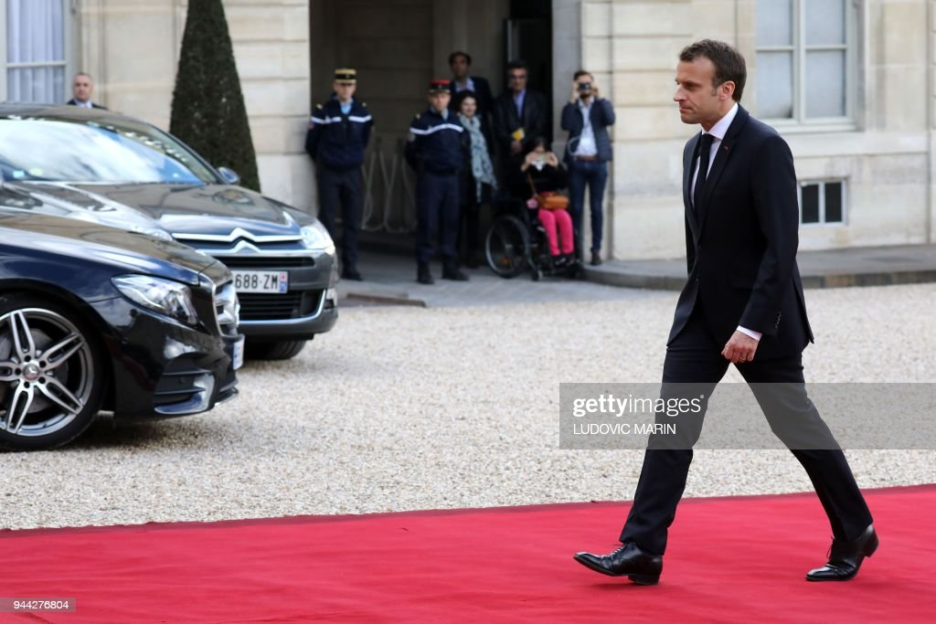 President Emmanuel Macron walks after a meeting with King of Morocco, on April 10, 2018 at the Elysee Palace in Paris. /