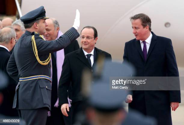 President Francois Hollande inspects the guard of honour as he arrives for a joint summit with Prime Minister David Cameron at RAF Brize Norton on...