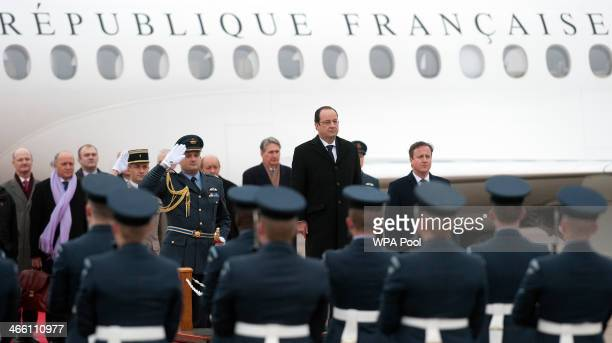 President Francois Hollande stands as he listens to the French national anthem played by a military band as he arrives to meet for a joint summit...