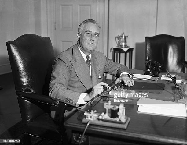 President Franklin D Roosevelt at his desk in the White House presses a key that sends an electric impulse across the continent to San Francisco...