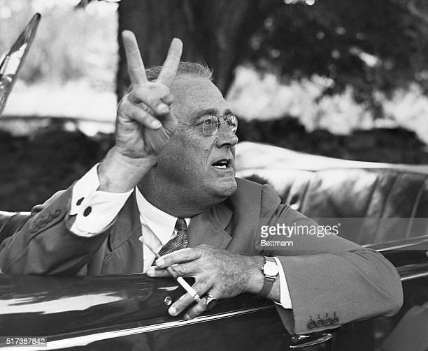 President Franklin D Roosevelt holds up two fingers to punctuate his reply to a corps of newspaper reporters on a tour of his Hyde Park estate Asked...