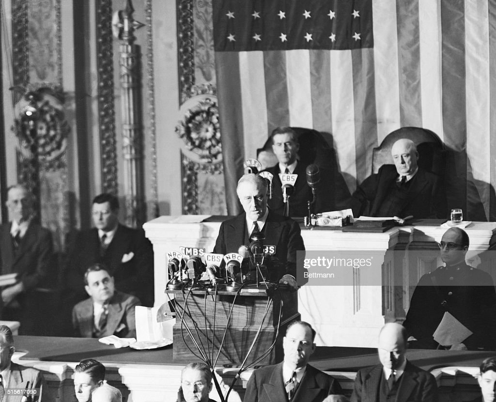 President Franklin D. Roosevelt is pictured during the dramatic moments before the joint session of Congress, December 8th, as he asked Congress to declare a state of war against Japan for its 'unprovoked and dastardly attack.' On the right is his son, James Roosevelt. In the background are Vice-President Henry A. Wallace (left) and Speaker of the House Sam Rayburn. Both the Senate and the House complied with his request almost immediately.