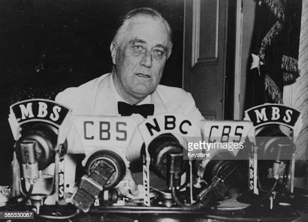 President Franklin D Roosevelt making a speech in front of a bank of microphones in which he is declaring an unlimited state of emergency during...