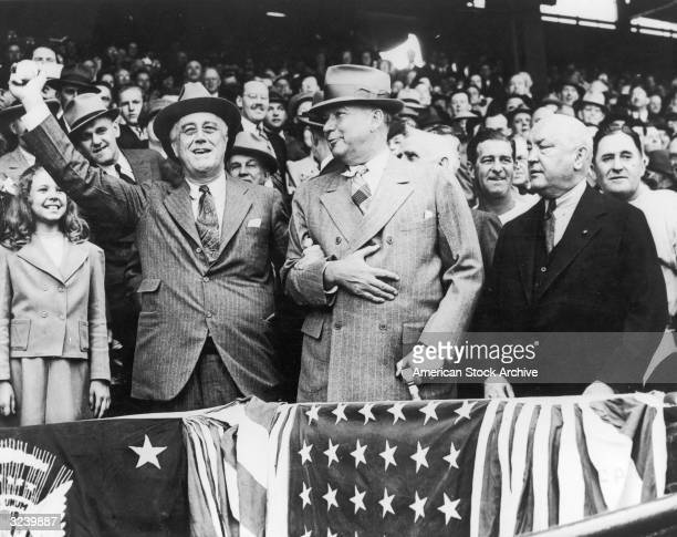 US president Franklin D Roosevelt prepares to throw the first ball of baseball season while gripping the arm of his Presidential Secretary General...