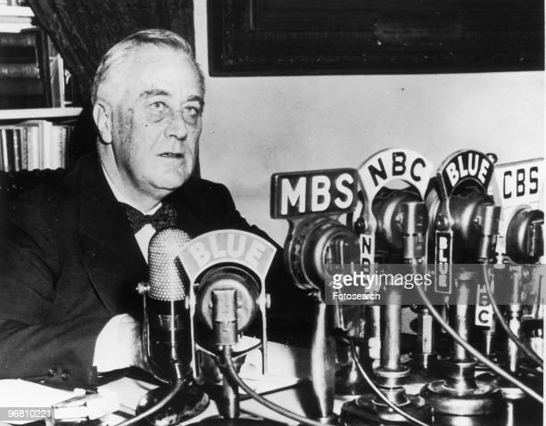 President Franklin D Roosevelt seated in front of a number of television and radio station microphones circa 1940s