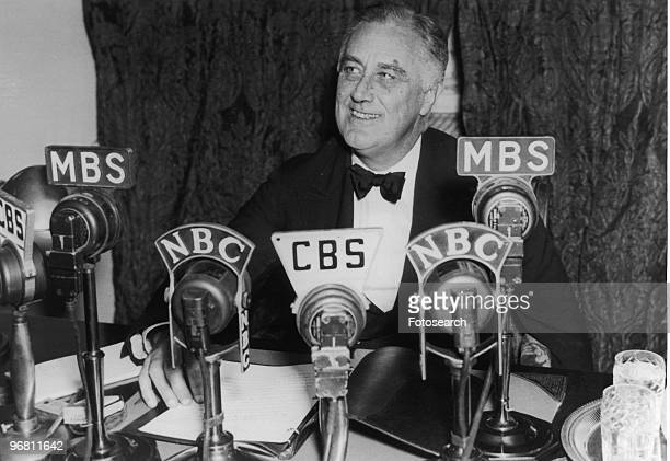 President Franklin D Roosevelt seated in front of a number of television and radio station microphones in Washington DC asking communities to...
