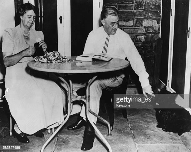 President Franklin D Roosevelt shaking the paw of his Scottie dog 'Falla' as his wife Eleanor knits beside him at their Hyde Park estate in New York...