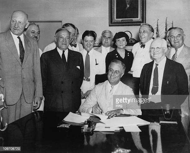 US President Franklin D Roosevelt signs the Social Security Act 14th August 1935 From left to right Robert Lee Doughton chairman of the House Ways...