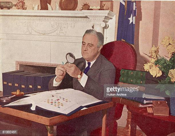 US President Franklin Delano Roosevelt holds a stamp under a magnifying glass while seated at his desk with his stamp collection Washington DC circa...