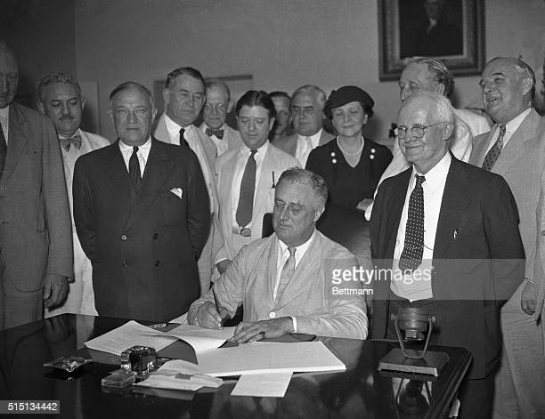 President Franklin Delano Roosevelt signs the Social Security Bill in the White House. Roosevelt is flanked by Senator Robert F. Wagner of New York...