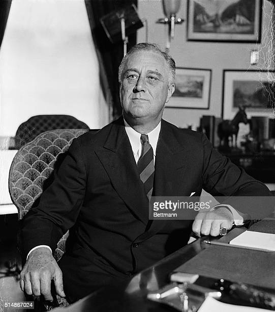 US President Franklin Delano Roosevelt sitting at his desk in the Oval Office