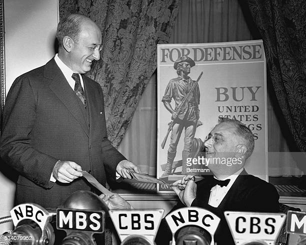 President Franklin Roosevelt buys the first of the U.S. Government's Defense Savings Bonds, from his Treasury Secretary Henry Morgenthau. FDR called...
