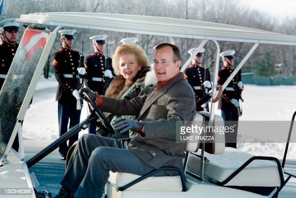 US President George Bush and British Prime Minister Margaret Thatcher drive away in a golf cart on November 24 1989 from the helicopter landing zone...