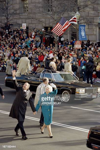 President George Bush and First Lady Barbara Bush walk down Pennsylvania Avenue and wave to the cheering crowd on January 20, 1989 in Washington, DC,...