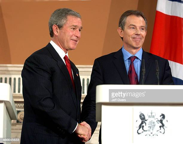 President George Bush and Prime Minister Tony Blair shaking hands at a press conference at the Foreign Office in London with the Stars and Strips and...