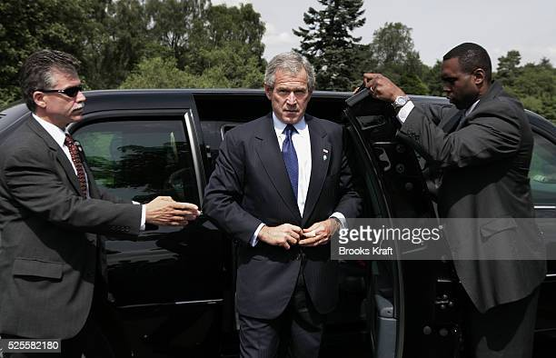 US President George Bush center gets out of his limousine surrounded by secret service agents as departs the G8 Summit at Gleneagles Scotland...