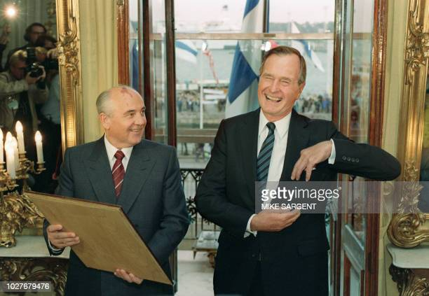US President George Bush laughs with Soviet President Mikhail Gorbachev as Soviet leader presents Mr Bush with a drawing 09 September 1990 after...