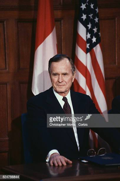 President George Bush listens to a reporter's question during a press conference in Ottawa. The President met with Canadian Prime Minister Brian...