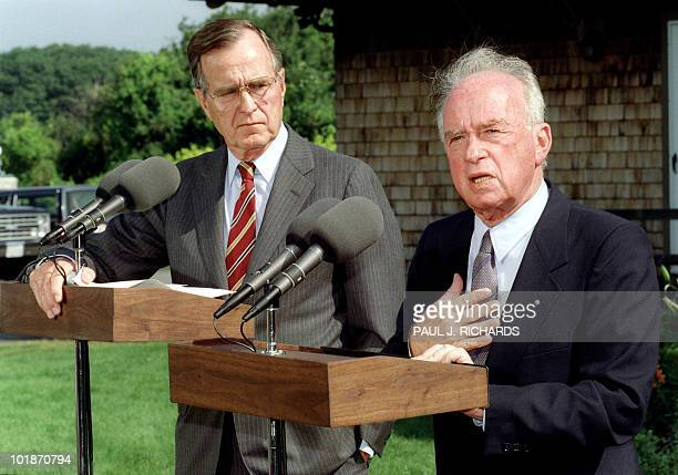 President George Bush listens to Israeli Prime Minister Yitzhak Rabin answer questions at a joint press conference, 11 August 1992, at Bush's...
