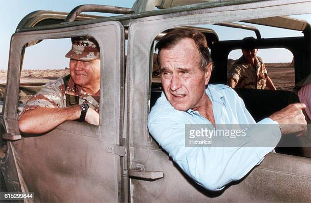 President George Bush and General Norman Schwarzkopf ride in a military vehicle in Saudi Arabia during Operation Desert Shield on November 22 during...