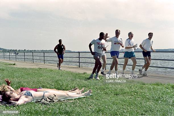 US President George Bush waves two women sunbathers as he jogs on August 1 1990 with actor Chuck Norris and his son Michael Norris at Haines Point in...