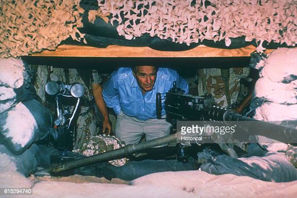 President George H W Bush peers out from a bunker at an M2 50caliber machine gun The president is in Saudi Arabia during the Thanksgiving holiday to...