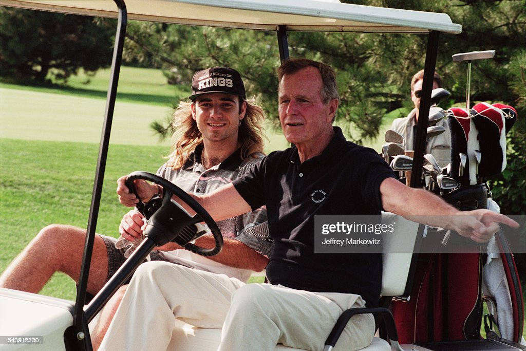 President George H. W. Bush plays golf with tennis player Andre Agassi.