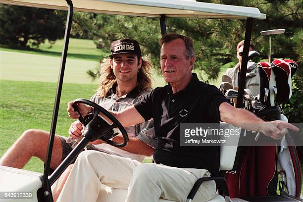 President George H W Bush plays golf with tennis player Andre Agassi