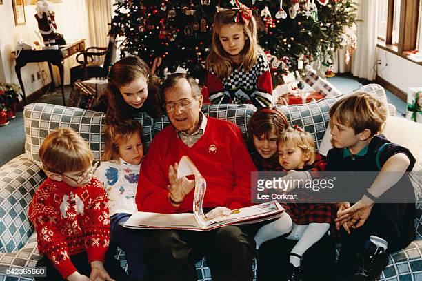 President George H W Bush reads to his grandchildren Pierce Marshall Barbara Lauren Jenna Ashley Bush and Sam LeBlond at Camp David on Christmas eve