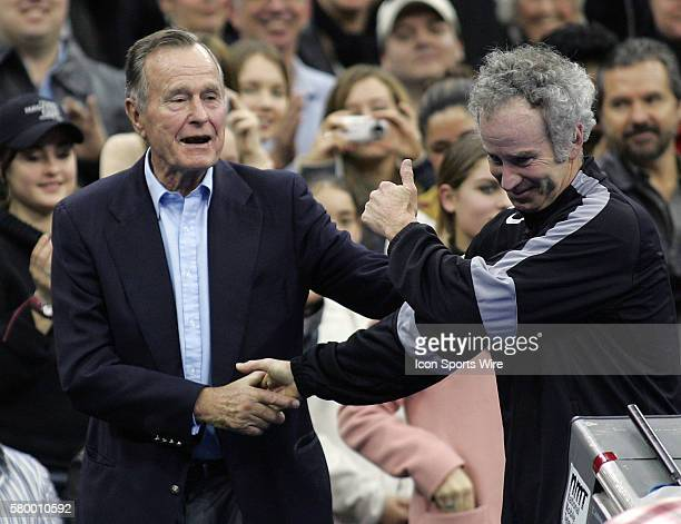 President George H W Bush shakes hands with John McEnroe before the Serving for Tsunami Relief tennis match at Toyota Center in Houston Texas Tennis...