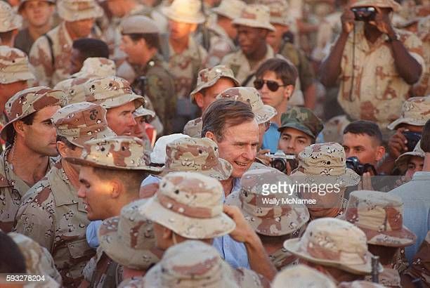 President George H W Bush surrounded by US troops in desert camo shakes hands while visiting troops in Saudi Arabia Thanksgiving Day 1990