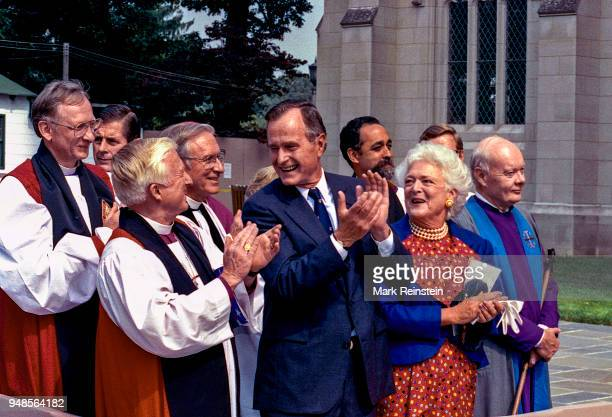 President George HW Bush and First Lady Barbara Bush , along with various unidentified religious leaders, applaud during the dedication ceremony of...