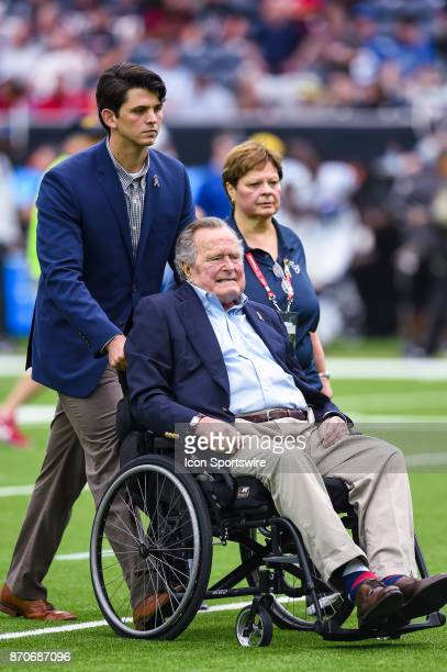 President George HW Bush leaves the field following the coin toss before the football game between the Indianapolis Colts and the Houston Texans on...