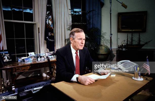 US President George HW Bush sits behind his desk in the White House's Oval Office Washington DC December 25 1991 He had just announced the...